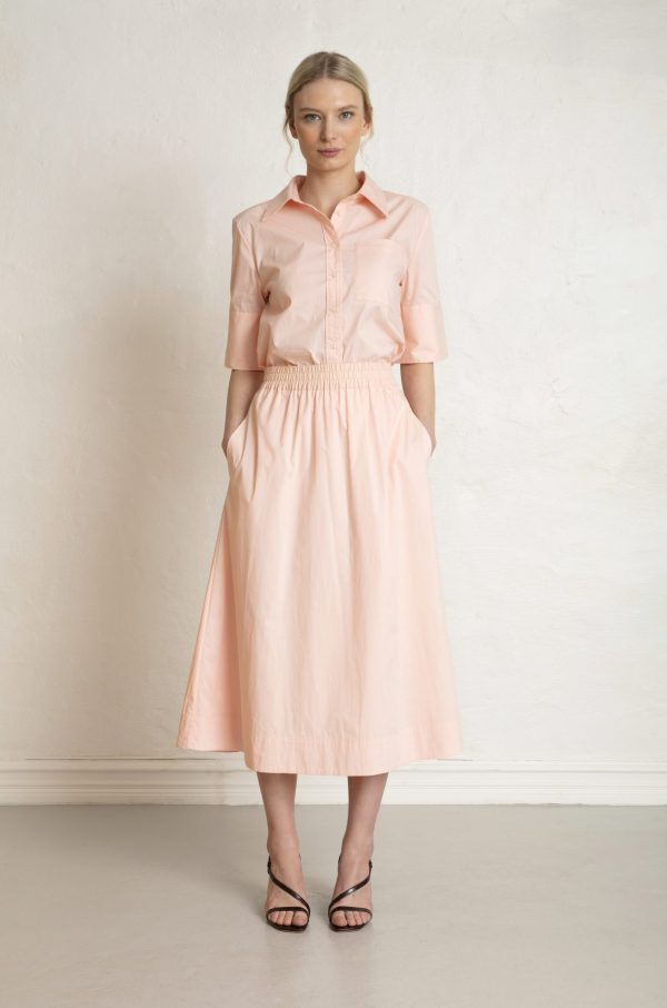 Woman in sustainable pink sateen skirt and shirt