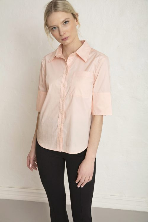 Girl in pink sateen shirt and black ecovero pants