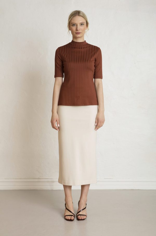 Woman in brown cinnamon top and white sustainable skirt