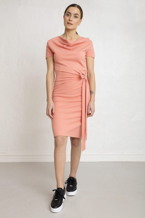 Woman in pink sustainable ecovero dress and sneakers