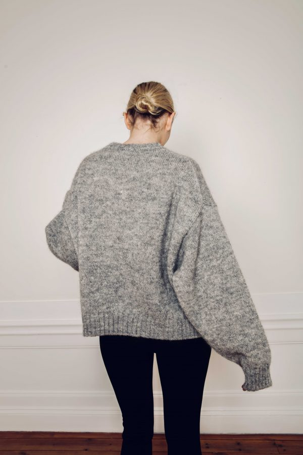 Girl wearing Ire chunky knitted grey sweater from behind