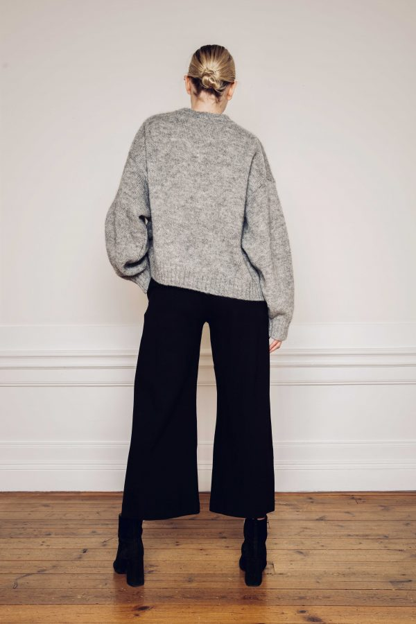 Ire knitted grey sweater with Lottie ecovero wide black pants styled with heel boots from the back