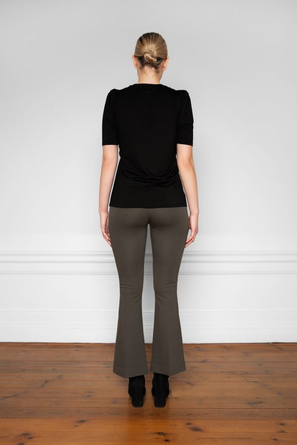 Girl wearing Lala Ecovero Flare Pants Ink Green with heel boots from the back