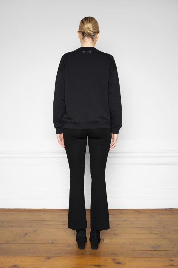 Girl wearing Ricon Sweatshirt in color Black with Lana Ecovero Flare Pants Black form the back