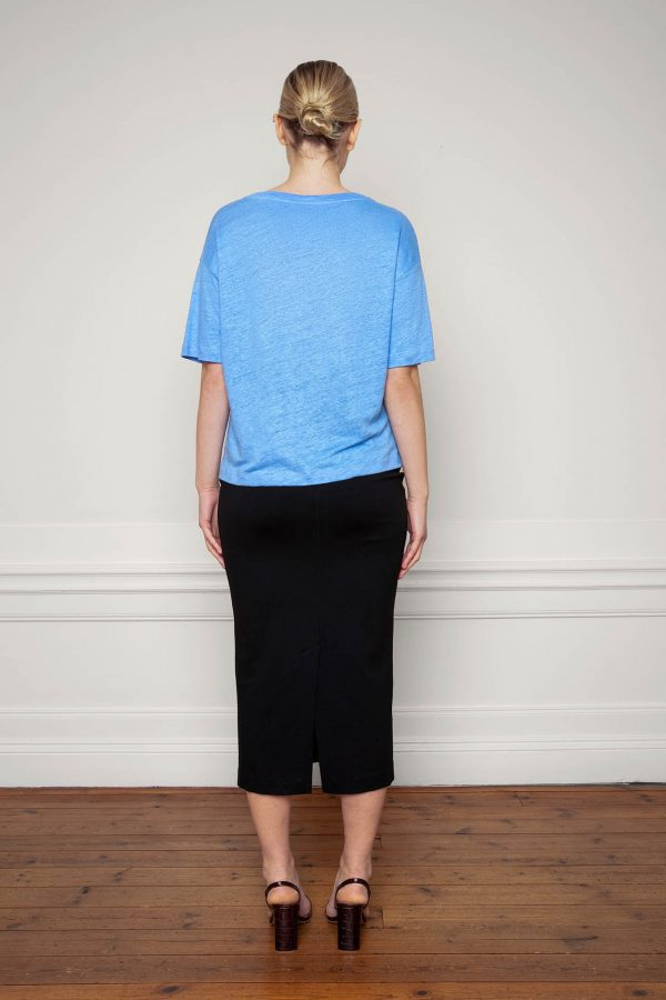 Girl wearing Raya Linen Tee Corn Blue with Lala Ecovero Skirt Black from the back